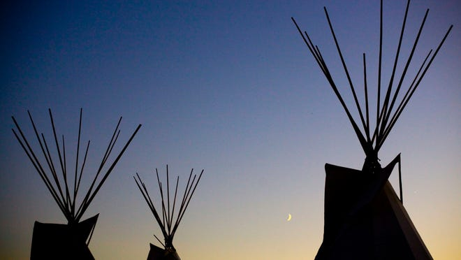 A cresent moon rises between lodges during the Kul Wicasa Pow Wow in Lower Brule, S.D., Aug. 13, 2010. Between 2007 and 2013, $25 million in aid to the tribe is unaccounted for, according to Human Rights Watch.