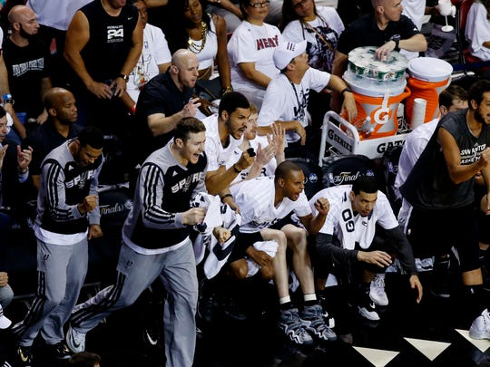 San Antonio Spurs players react during the third quarter of game four of the 2014 NBA Finals against the Miami Heat at American Airlines Arena.