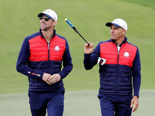 Olympic swimmer Michael Phelps and surfer Kelly Slater walk up a fairway during the 2016 Ryder Cup Celebrity Matches at Hazeltine National Golf Club on Sept. 27 in Chaska, Minn.