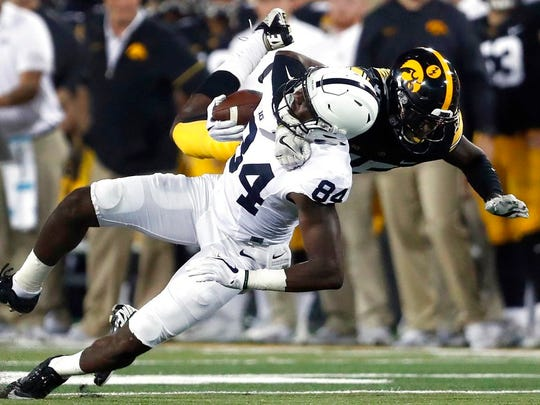 Penn State wide receiver Juwan Johnson, left, is pulled down by Iowa defensive back Joshua Jackson after catching a pass during the first half of an NCAA college football game Saturday, Sept. 23, 2017, in Iowa City, Iowa. (AP Photo/Jeff Roberson)