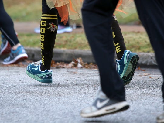 Sporting festive socks, Tina Todd runs during the 12th annual Turkey Day 5K in Jackson, Tenn., on Thursday, Nov. 24, 2016.