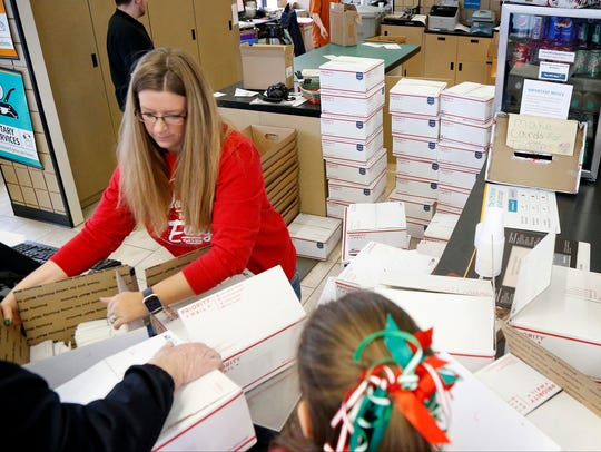 More than 65 boxes filled with holiday cards sit behind