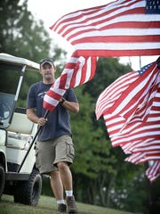 Travis Goebel secures American flags to the fence posts