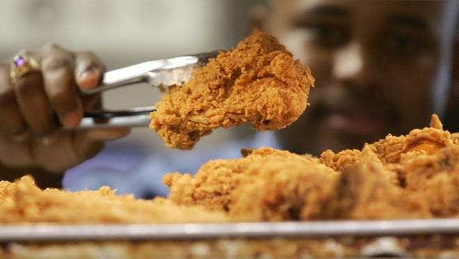 In this Monday, Oct. 30, 2006 photo, a Kentucky Fried Chicken employee uses tongs to hold up an sample of the company's trans fat-free Extra Crispy fried chicken in New York.