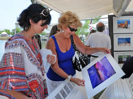 FILE PHOTO: Sharon Warren of Bethany Beach, center, and her daughter, Audrey Warren, enjoy works by fine art photographer George Rhodes of Plantation, Florida, during a previous Art's Alive fine art show at Northside Park. This year's event happens June 24-25, 2017.
