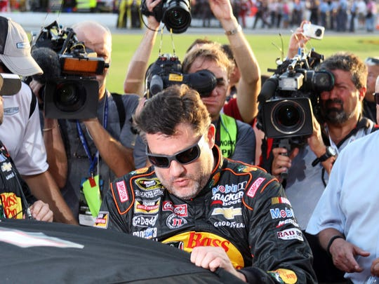 Tony Stewart climbs into his car to start a NASCAR Sprint Cup auto race at Atlanta Motor Speedway,  Aug. 31, 2014, in his first event since his sprint car struck and killed a fellow driver.