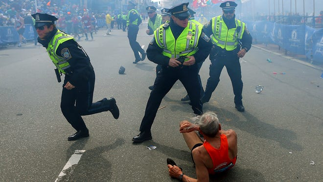 Bill Iffrig lies on the ground as police officers react to a second explosion at the finish line of the Boston Marathon on April 15, 2013.