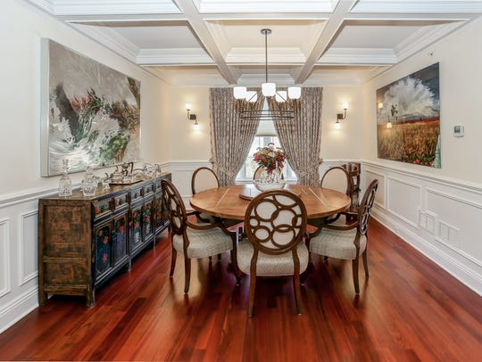 The dining room features wainscoting, hardwood floors