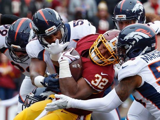 Washington Redskins running back Samaje Perine (32) tries to make headway against the Denver Broncos defense during the first half an NFL football game in Landover, Md., Sunday, Dec 24, 2017. (AP Photo/Alex Brandon)