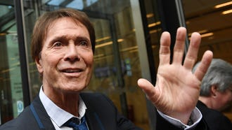 Sir Cliff Richard waves as he arrives at the High Court in London, July 18, 2018.