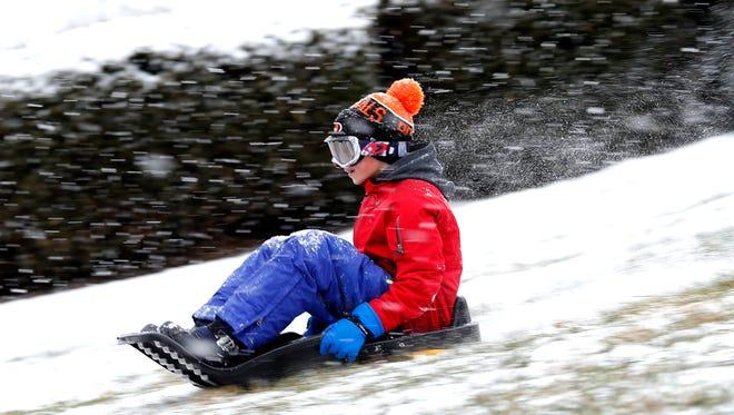 Sam Hoard, 10, of Hyde Park, sleds down the hill at Ault Park in the Hyde Park neighborhood of Cincinnati on Thursday, Jan. 5, 2017.