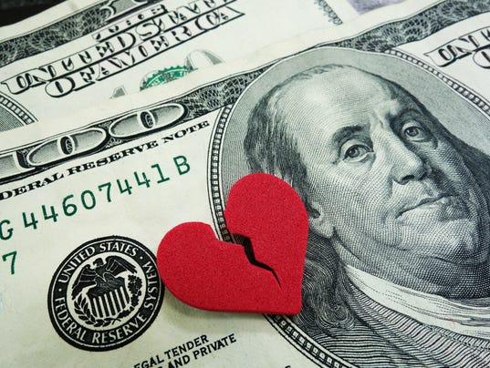 A broken red heart over two US hundred dollar bills