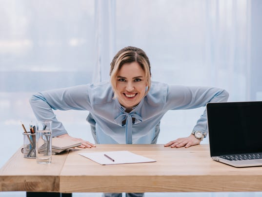 happy businesswoman doing push up on table at office