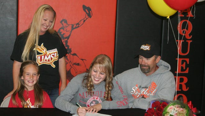 Fernley's Serena Olson smiles as she signs a letter of intent to play softball for the University of Missouri-St. Louis. With her are her sister Jenna Watson, mom Sarah Watson and dad Jason Watson.
