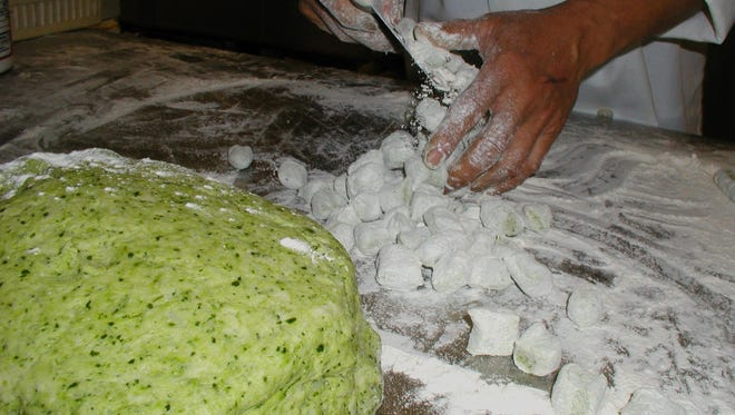 Spinach gnocchi starts as a big greenish ball of dough that the chef cuts chunks from, kneads, flattens, cuts into strips and cross-cuts into bite-sized dumplings. A coating of flour keeps the gnocchi from sticking together. The batch will be kept in a freezer until ordered.