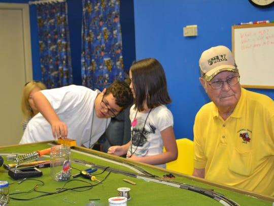 Christian Chiles (left), 15, and Brynna Street, 9, look at a model train on a track at the Alexandria T.R.E.E. House Children's Museum's Junior Engineer Camp on Tuesday. Bill Taylor (center) with the Rockwell Railroad teaches them how to operate two trains on the same track on the first day of the camp.