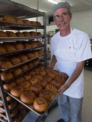 Todd Johnson, the owner of the Artisan Bread Company, shows some brioche buns baked earlier in the morning at his Fowler Street establishment Tuesday, the official opening day of the business.