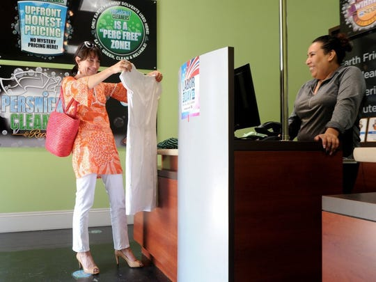 Kristin Mayville, left, of Ventura, looks at her dress for stains before handing it to Viridiana Hernandez, a clerk at Persnickity Dry Cleaners in Ventura.