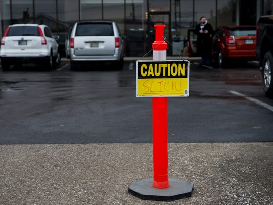 A sign warning cars of the icy conditions in a parking lot on John Street in Evansville on Wednesday.