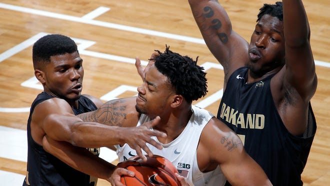 Michigan State's Nick Ward is pressured by Oakland's Stevie Clark, left, and Xavier Hill-Mais during the first half Wednesday, Dec. 21, 2016, in East Lansing.