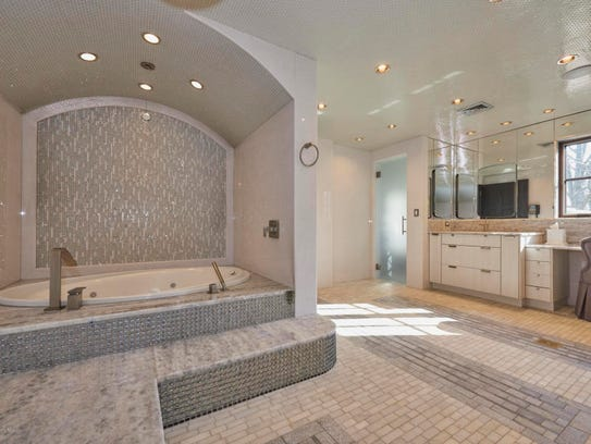 In the Master bathroom features a custom sink with an exquisite whirlpool with marble and tile.