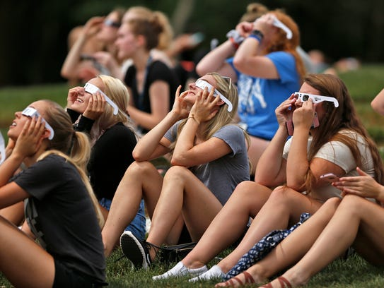 Students look up at the peak of the solar eclipse,