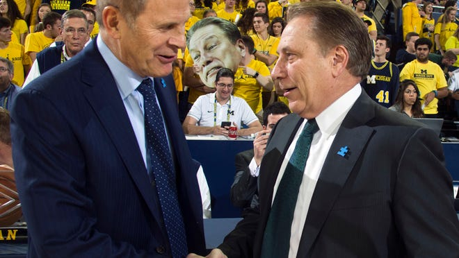 FILE - In this Feb. 7, 2017, file photo, Michigan head coach John Beilein, left, shakes hands with Michigan State head coach Tom Izzo before an NCAA college basketball game at Crisler Center in Ann Arbor, Mich.  No. 4 Michigan State and Michigan will meet Saturday in the rivals' only scheduled matchup. (AP Photo/Tony Ding, File)