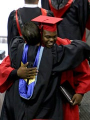 Michael Nash receives a hug from Wichita Falls High Principal Christy Nash after walking across the stage during the graduation ceremony Saturday afternoon at Kay Yeager Coliseum.