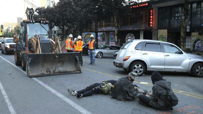Protesters lie down and sit in the street after workers and heavy equipment from the Seattle Department of Transportation arrived at the the CHOP (Capitol Hill Occupied Protest) zone in Seattle, Friday, June 26, 2020, with the intention of removing barricades that had been set up in the area. Several blocks in the area have been occupied by protesters since Seattle Police pulled back from their East Precinct building following violent clashes with demonstrators earlier in the month.