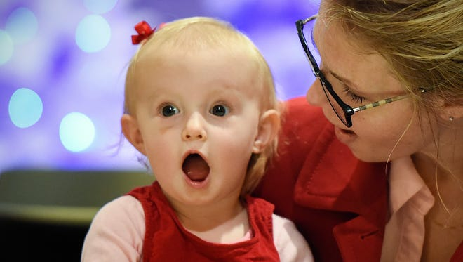 Tori Heidebrink, 1, lets out a scream when she sees St. Nicholas enter the room while doing an art project with her mom Heather Hammond at KringleFest Saturday, Dec. 3, at the Stearns History Museum.