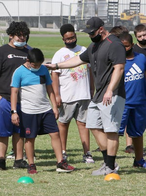 Darby Junior High School football coach Carl Neumeier works with his offensive line players, Tuesday, July 14, 2020, during practice at the Northside school.