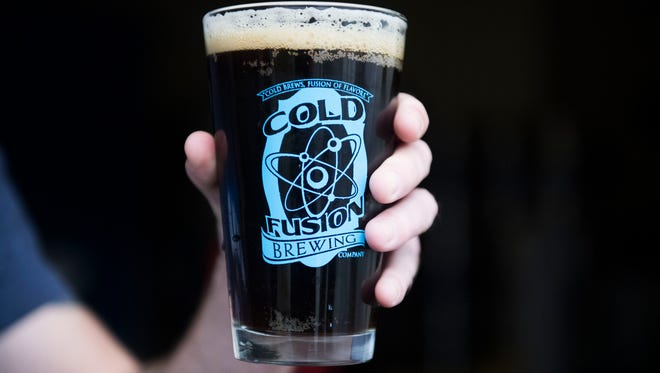 """Adam Privett, co-owner and head brewer of Cold Fusion Brewing, holds a pint of """"Dark Matter"""" at the brewery in North Knoxville, Tuesday, Dec. 5, 2017. Cold Fusion will be at the inaugural Brawny Beer Festival this Sunday, Dec. 10, held at the Mill and Mine in downtown Knoxville."""