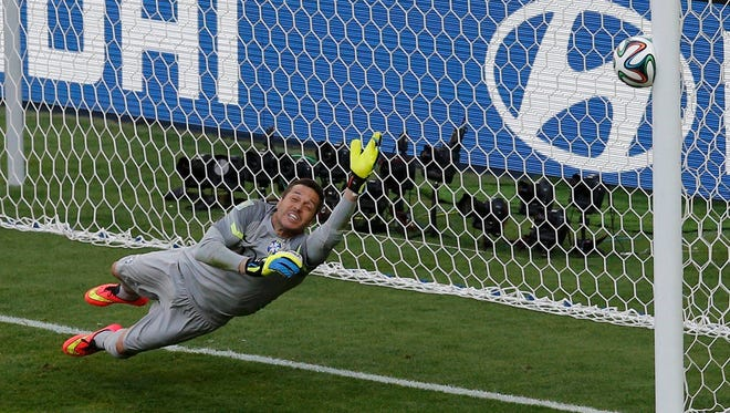 Brazil goalkeeper Julio Cesar dives as the decisive penalty shot by Chile's Gonzalo Jara hits the goal post in the penalty shootout during their 2014 World Cup round of 16 game at the Mineirao stadium in Belo Horizonte.