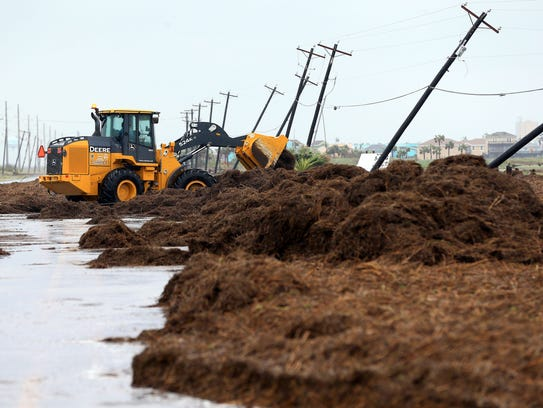 Crews clear debris from State Highway 361 in Port Aransas on Saturday, Aug. 26, 2017 after Hurricane Harvey  made landfall in the Coastal Bend area.