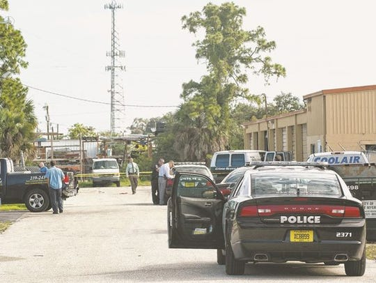 Fort Myers police officials investigate the scene where a man's body was found behind a Dumpster at Budget Truck Rental on Powell Street on Thursday morning.