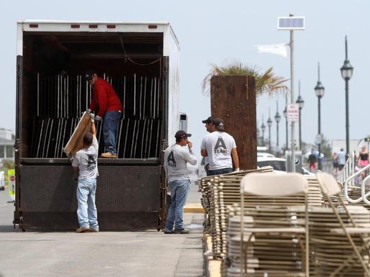 Workers remove tables from Ocean Avenue on Monday, a day after crowds attending Belmar's annual Seafood Festival forced borough officials to block all traffic from entering town via Route 35 for four hours.