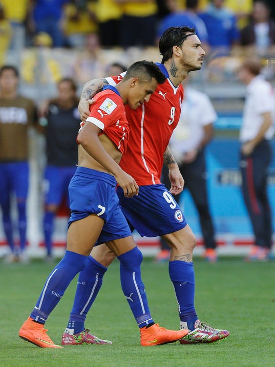 Chile's Alexis Sanchez, left, walks with  his teammate Mauricio Pinilla after missing his shot during a penalty shootout following regulation time during the World Cup round of 16 soccer match between Brazil and Chile at the Mineirao Stadium in Belo Horizonte, Brazil, Saturday, June 28, 2014. Brazil won 3-2 on penalties after a 1-1 tie. (AP Photo/Ricardo Mazalan)