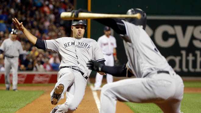 New York Yankees' Gary Sanchez slides to the plate to score on a sacrifice fly by Billy Butler, as teammate Didi Gregorius, right, gestures in the first inning of a baseball game against the Boston Red Sox at Fenway Park, Thursday, Sept. 15, 2016, in Boston.