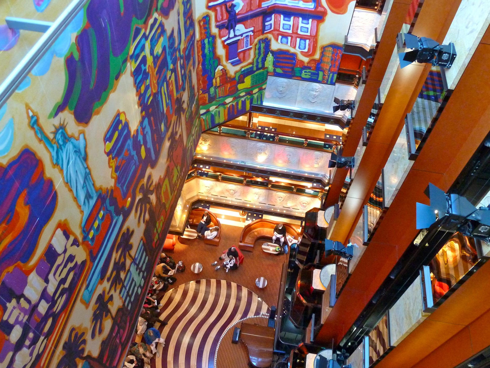 "From the ""heart"" of the ship, the Atrium America spans a dizzying nine-deck height. Along its forward bulkhead, there is a colorful mural by Alaskan artist Devita Writer depicting 10 famous U.S. destinations."