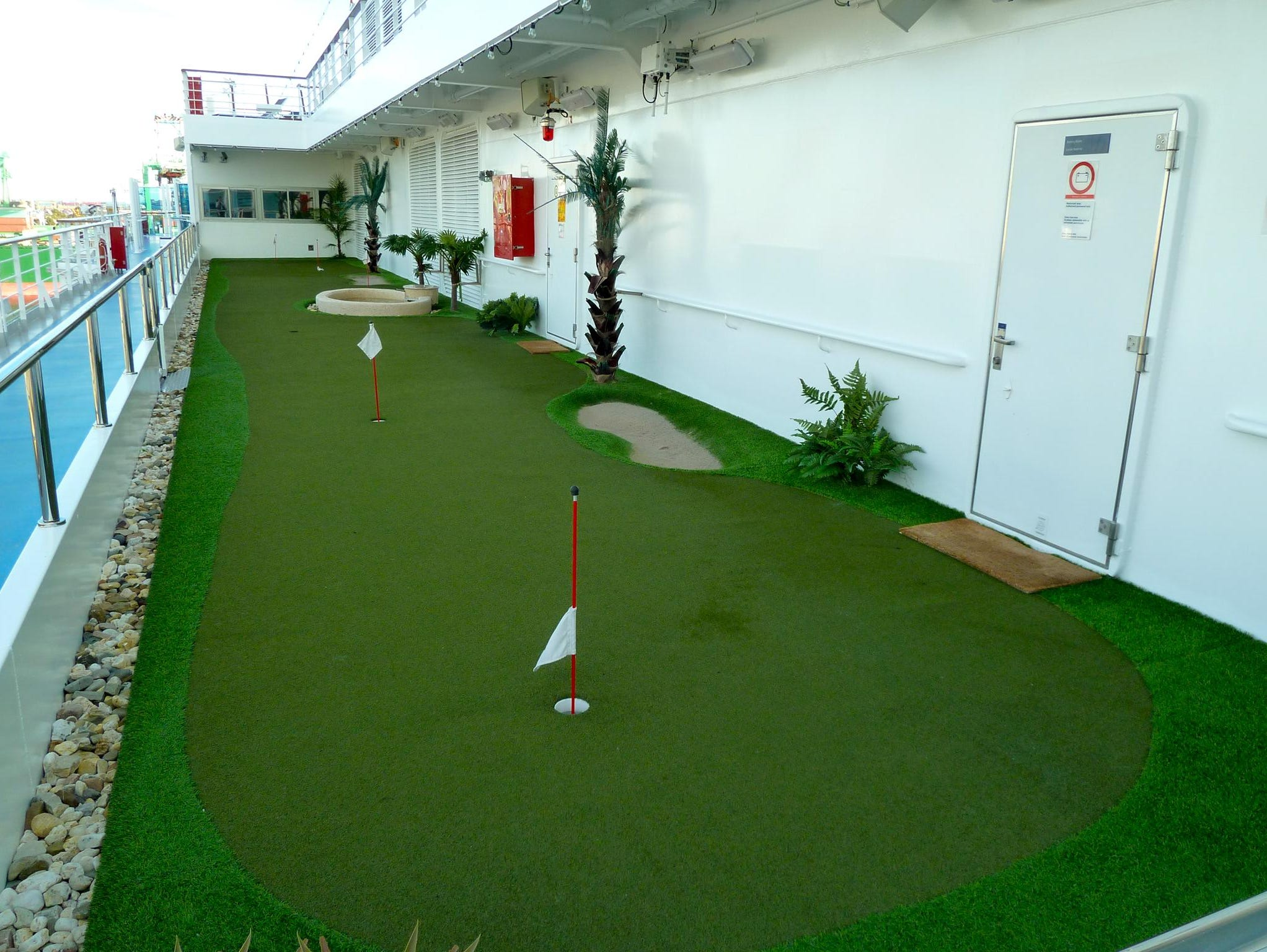 On the starboard side of Magnolia Deck, there is a mini-golf course adjacent to a virtual golf simulator.