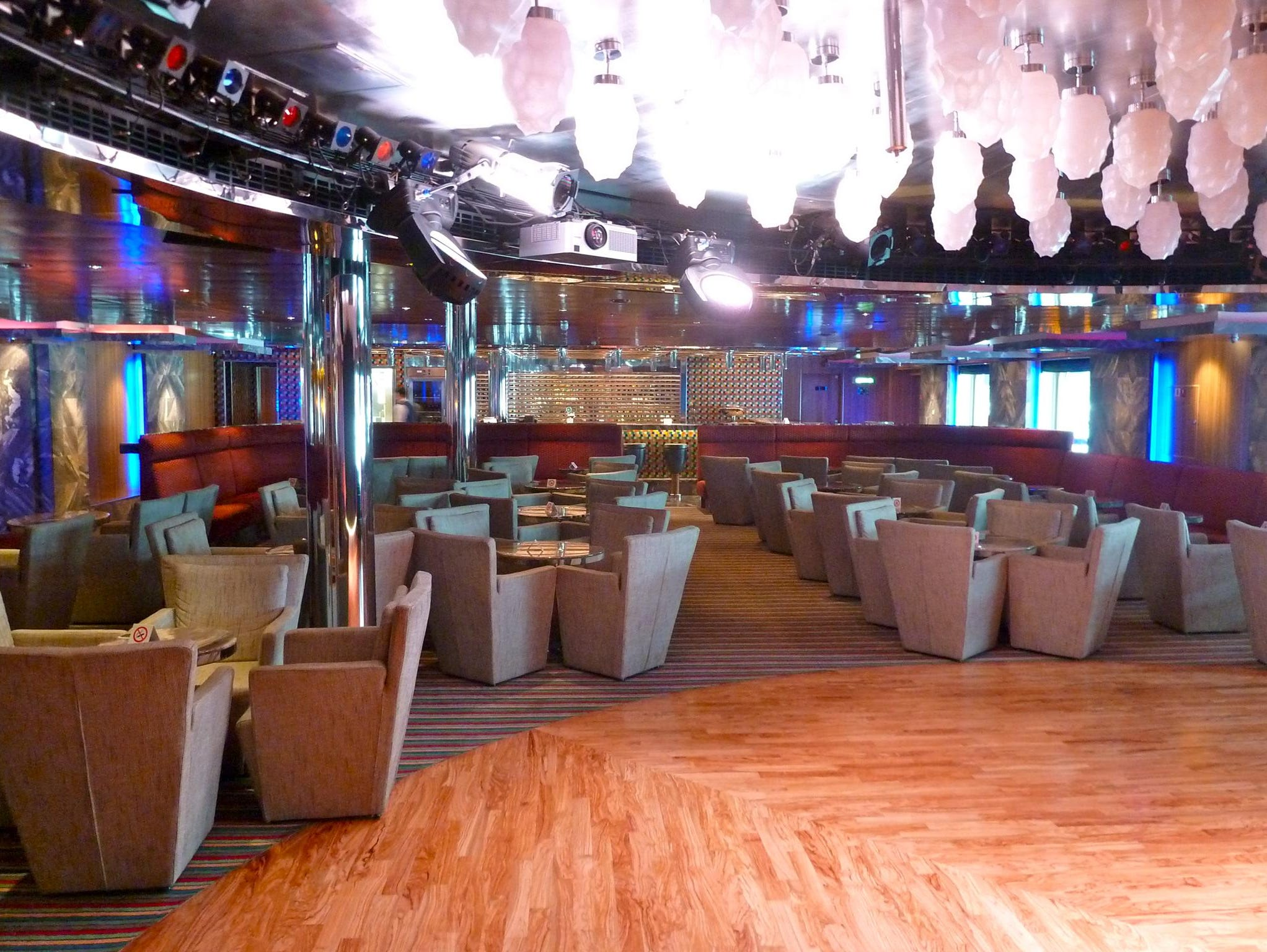 """The Excite Piano Bar is located on the port side of Azalea Deck and features a small stage for cabaret-style performances, edgy """"modern"""" seating and clusters of blown-glass chandeliers."""