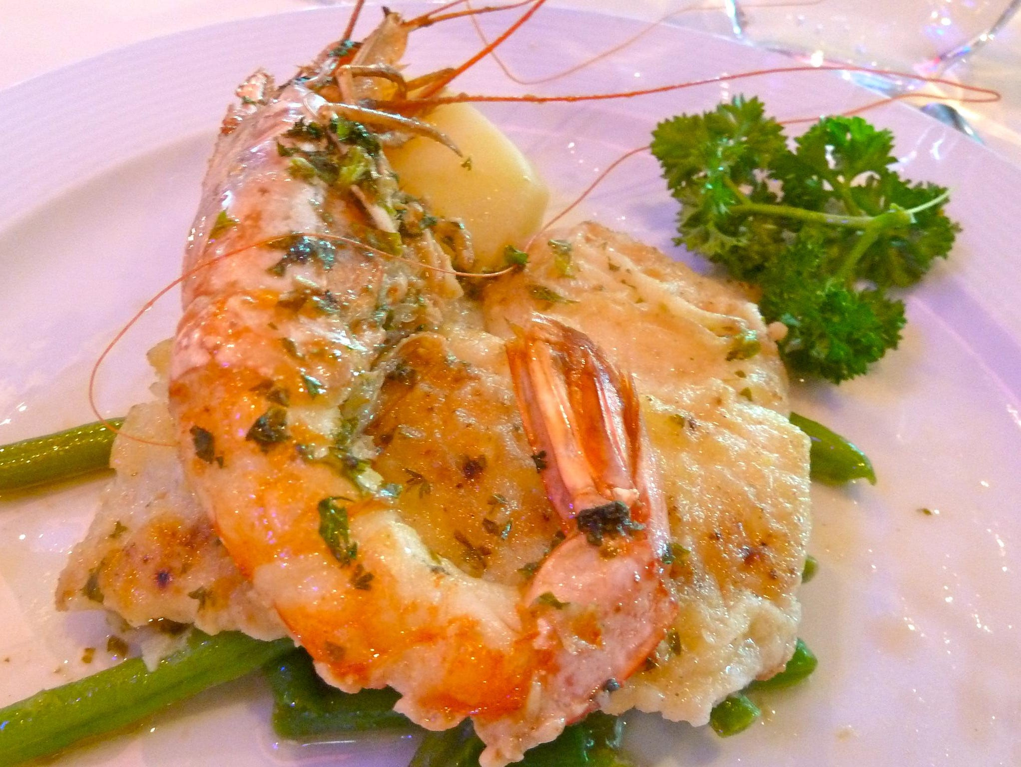 Costa ships are known for their fresh fish and seafood entrées, such as this prawn-topped tilapia.