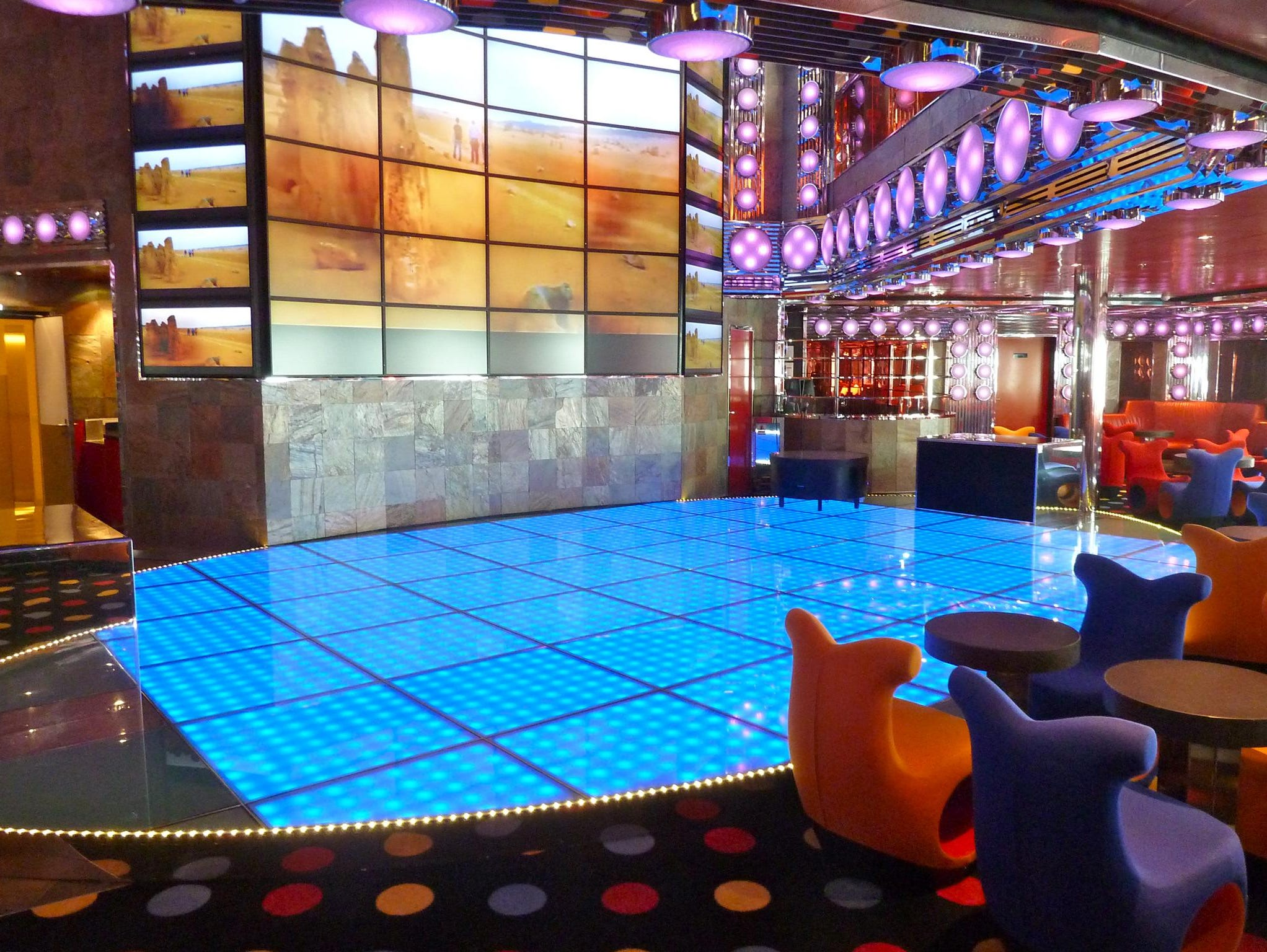 """Inboard of the Lounge and Bar Alcazar on Gardenia Deck, there is the lower level of the double-deck Discoteca Shaharazad (Farsi and Arabic for """"city dweller""""), which features a fiber-optic acrylic dance floor, vivid polka dots and pulsating lavender and blue lighting."""