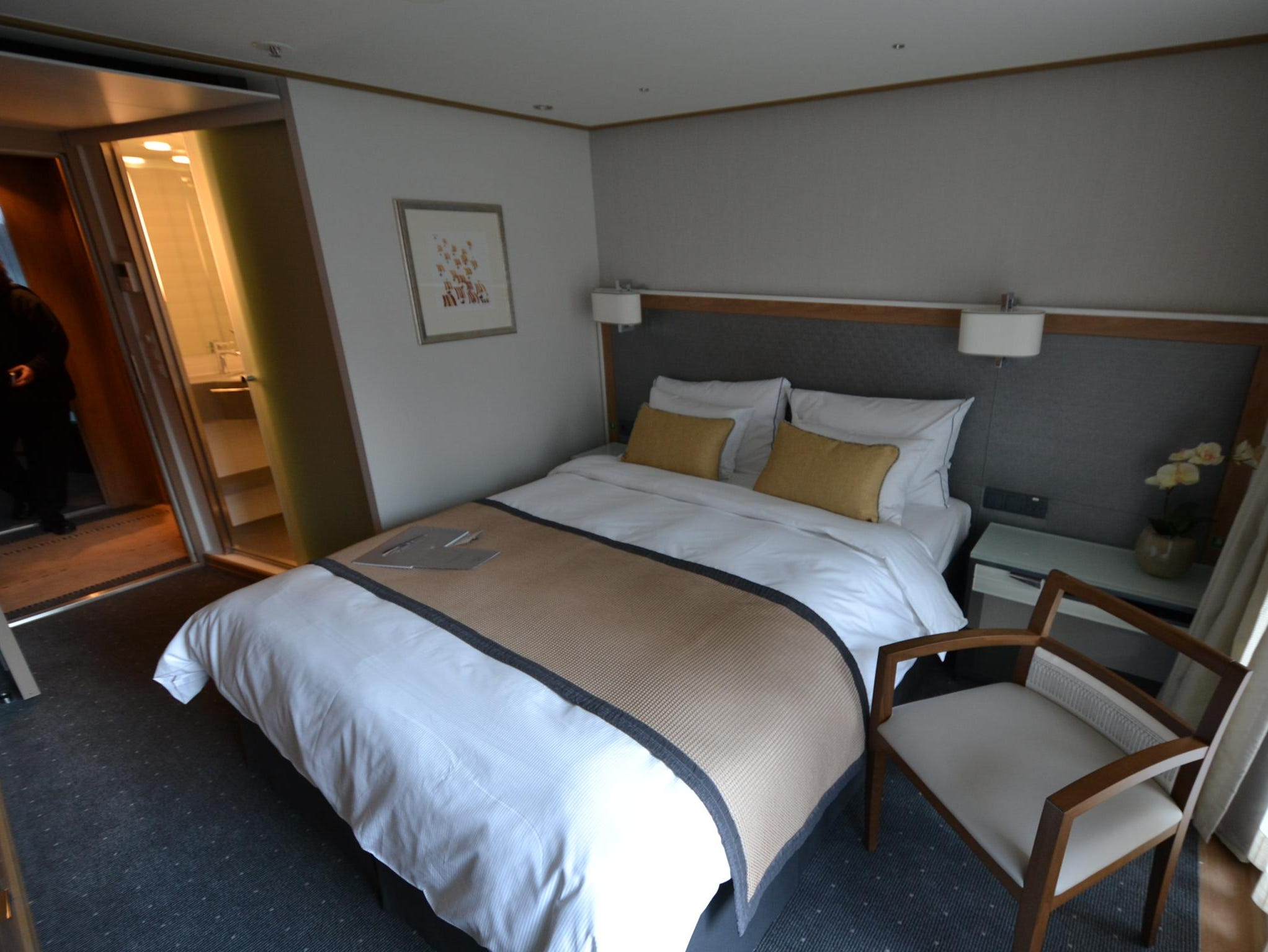 The interior of Veranda Staterooms have a bed, chair, side table, a desk area and a flat-panel television.