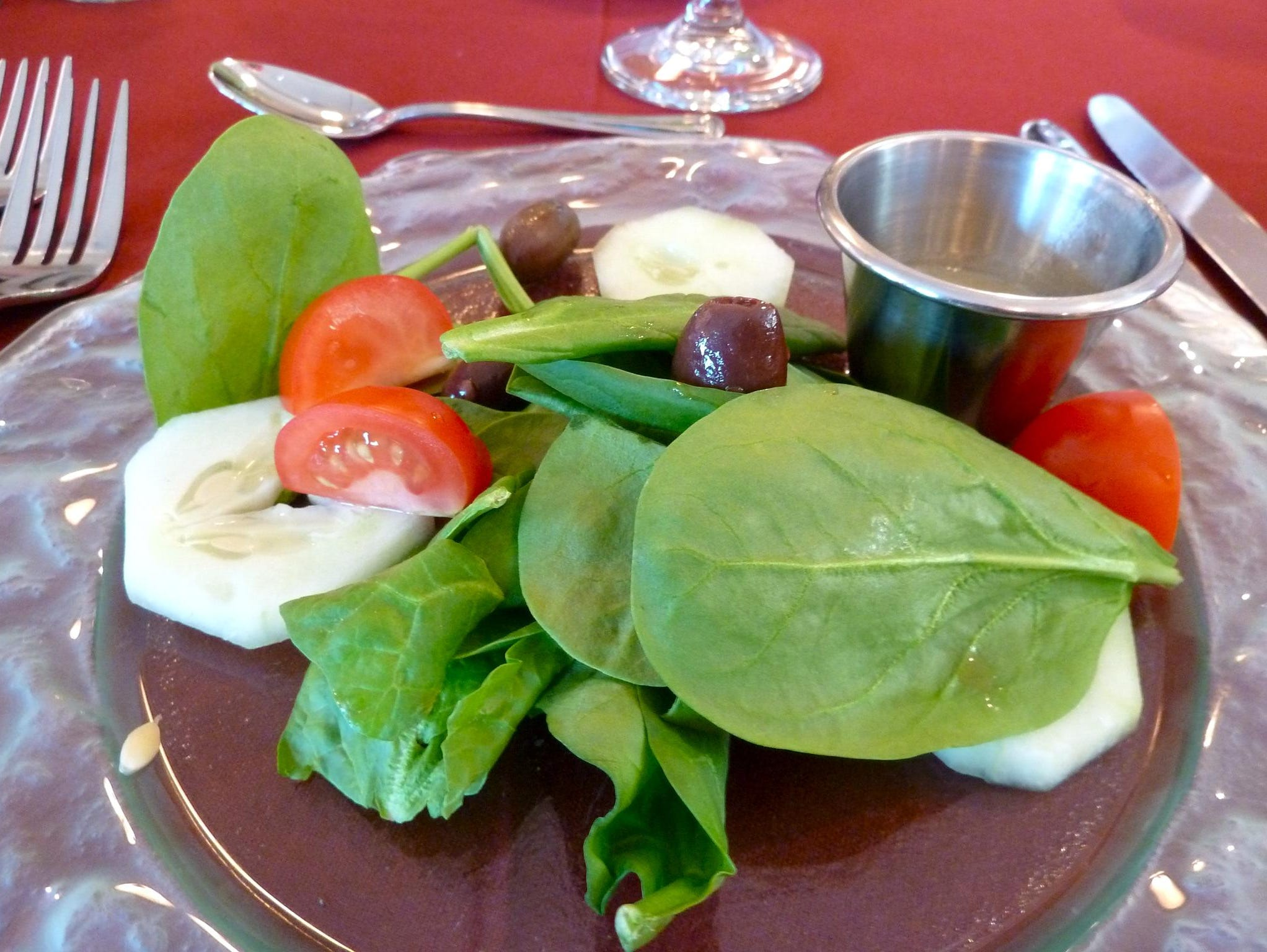 Dinners begin with freshly baked breads and a salad of the day, such as this spinach salad with kalamata olives dressed with balsamic vinegar and olive oil.