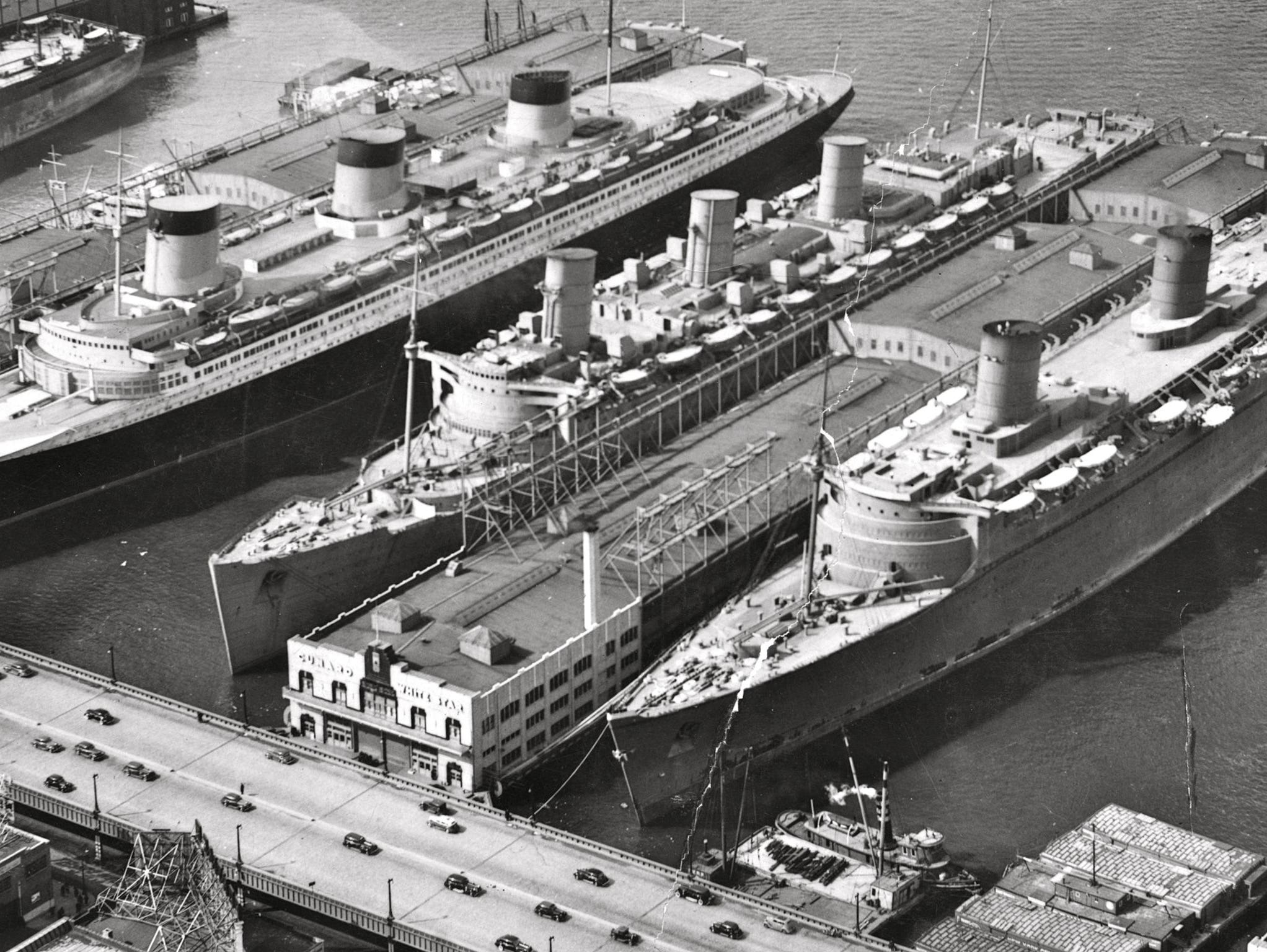 In September 1939, with the outbreak of war in Europe, the Queen Mary was laid up at New York along with the Normandie (left). In March of 1940, they were joined by the brand new Queen Elizabeth (right) for the only gathering of the world's first 'thousand footers.' All were slated for Allied trooping duties but the Normandie was tragically destroyed by fire in 1942.