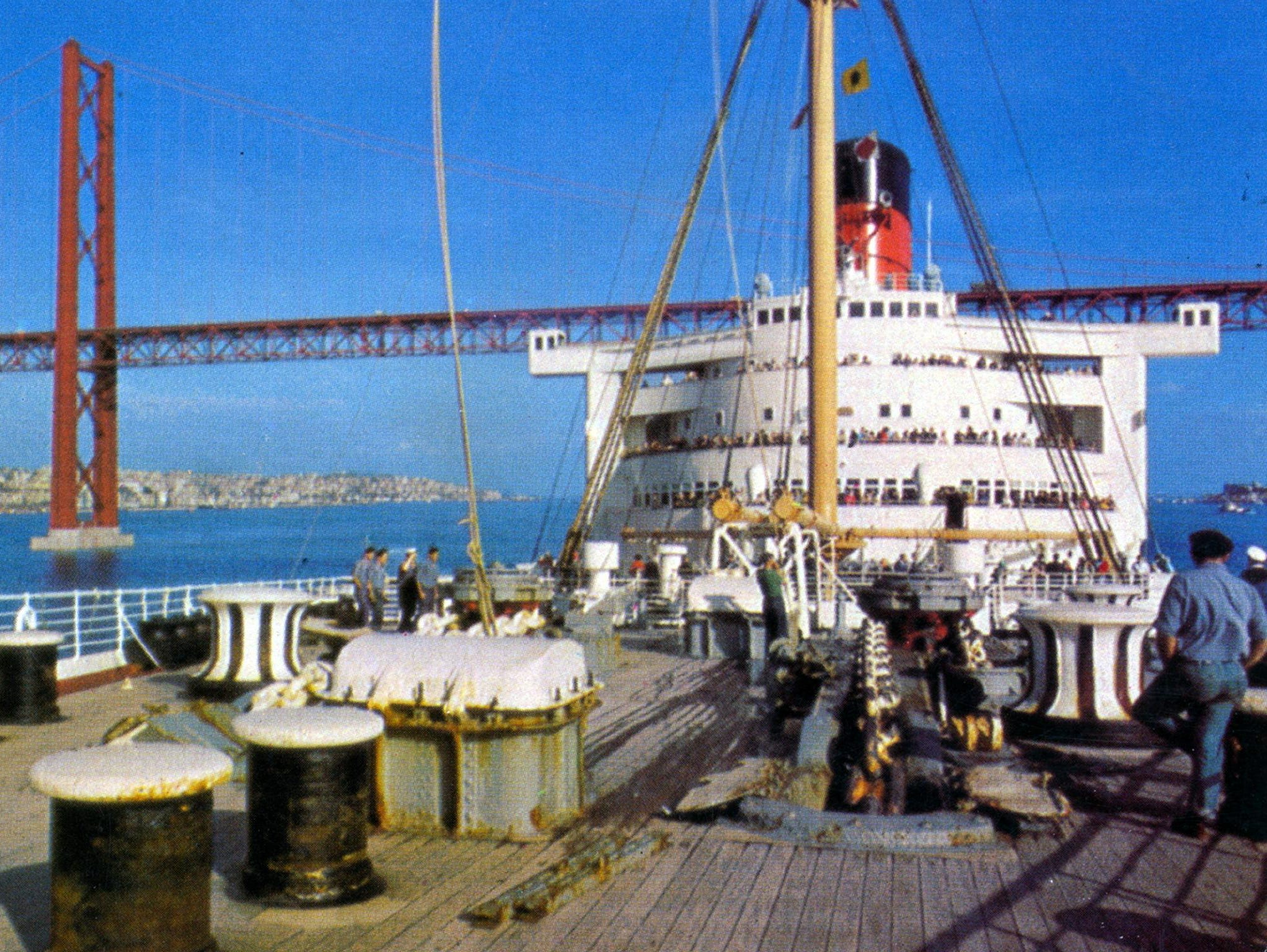 The Queen Mary's final, 1001st crossing took place in September of 1967. It was sold to the City of Long Beach for $3.5 million and departed on a 39-night delivery cruise around South America. In this unusual image, the Mary is shown sailing under Lisbon's Tagus Bridge.