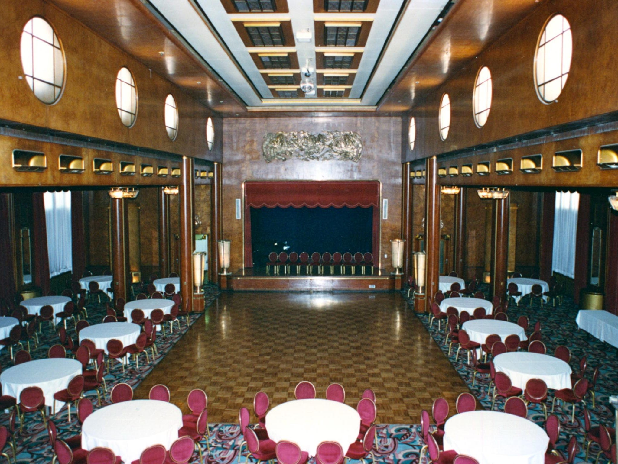 The soaring Queen's Salon is the former first-class lounge. If the 30-foot-high central ceiling looks familiar, that's because it inspired the set that went topsy turvy inThe Poseidon Adventurewhere a number of extras and a Christmas tree plunged into the glass fixtures.