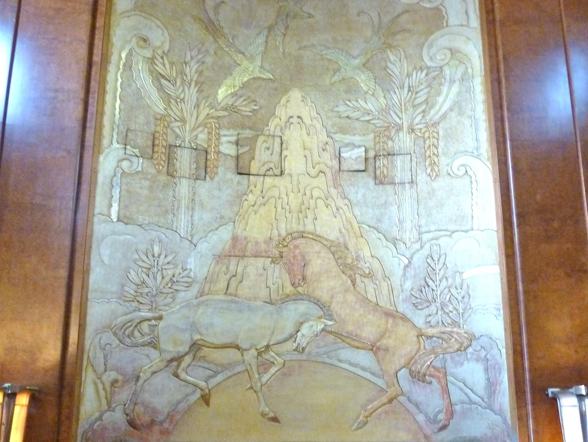 Here is a closer view of the fireplace and Art Deco jousting unicorn panel, one of the finest works of art commissioned for the Queen Mary or any ship, for that matter. Note the five small movie projector doors.