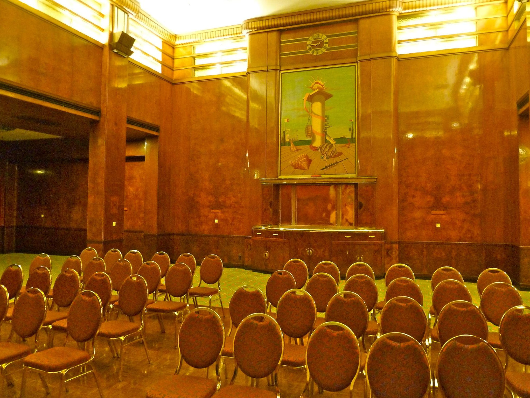 The brown oak-paneled Royal Salon follows the Queens Salon on Promenade Deck. The former first-class Smoking Room is another towering banquet and convention space. Its main focal points are two oil paintings by Edward Wadsworth. This is a view facing aft.